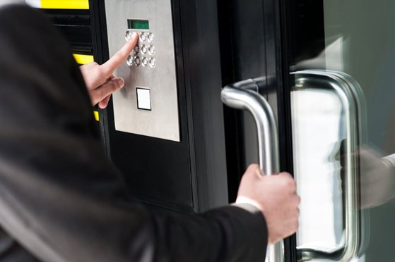 Man entering security code into business door