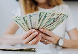 Life Insurance as part of your financial plan: A person holds American banknotes in a fan
