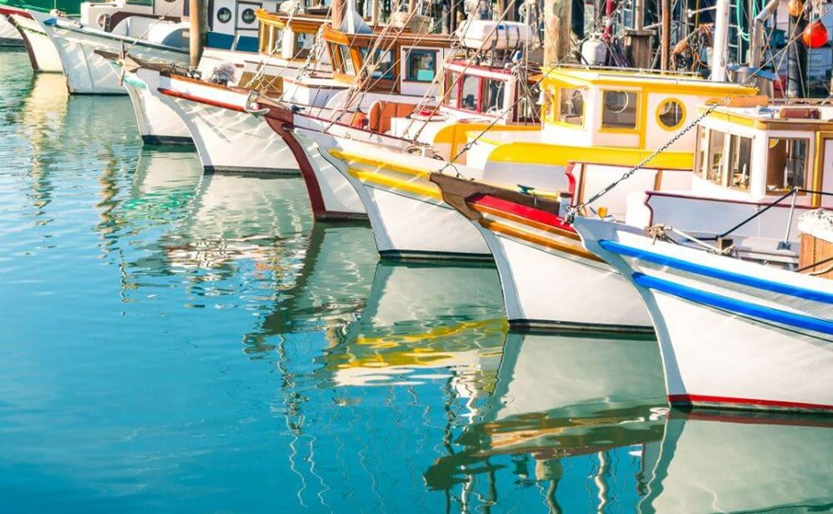 row of colorful boats on water