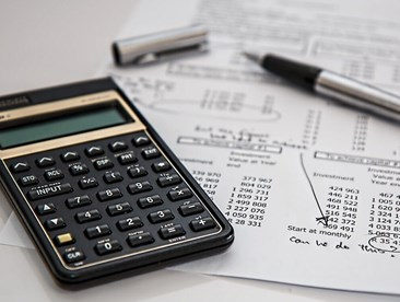 Insurance deductibles A calculator and paperwork are pictured on a desk