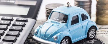 Close up blue car with calculator and coins