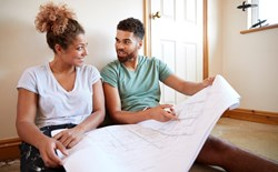 couple sitting on floor looking at floor plans