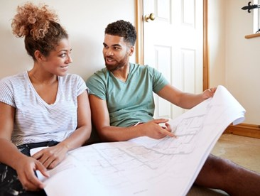 couple-sitting-on-floor-looking-at-plans-in-empty-room-of-new-home