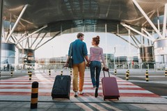 couple with travel suitcases holding hands walking into airport