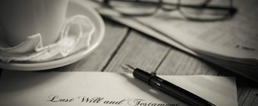 last will and testament with pen cup and glasses in black and white