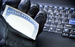 gloved hand holding blank Social Security card over computer keyboard