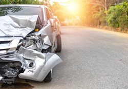Crashed gray car on road backlit by sun
