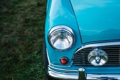 front of aqua blue classic car with headlight hood fender tire and bumper