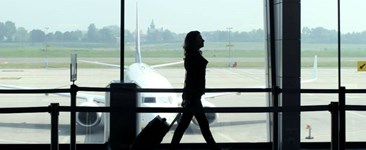 silhouette of woman with rolling luggage in airport walking past plane