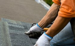 gloved worker installing shingles on roof