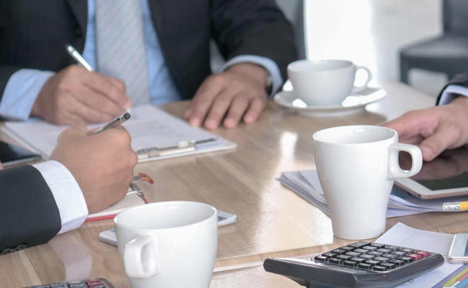 hands of businessmen around table at meeting with coffee cups notepads and calculator