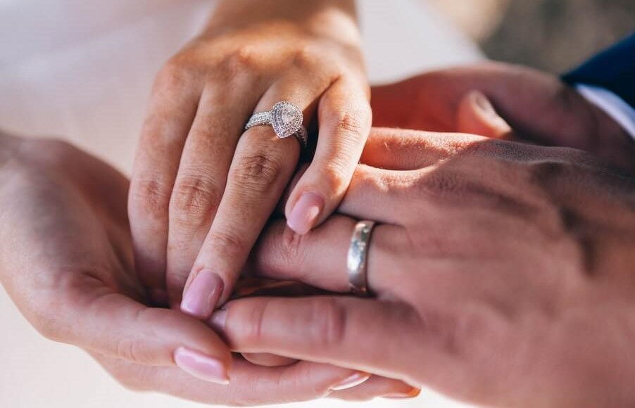 Insurance tips for newlyweds a couple wearing wedding rings show clasp hands