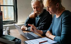 adult couple looking at laptop and insurance forms together