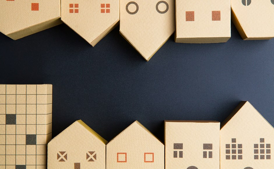 rows of small cardboard houses on a black background