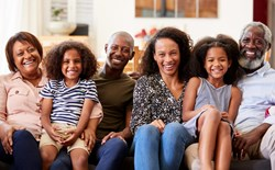 The perfect age to buy a life insurance policy: multigenerational family sits on a couch