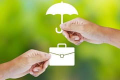 hands holding white umbrella over white suitcase on green background