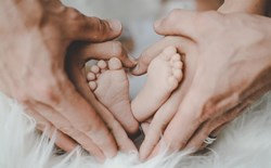 babys feet with parents hands forming hearts around them