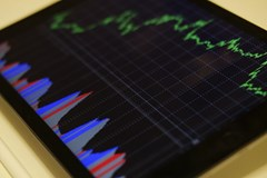 How insurance companies make money: a graph of profits is shown on a tablet screen