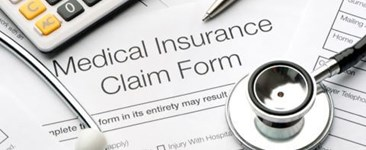 medical insurance claim form with stethoscope pen and calculator